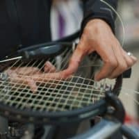 Stringing Machine. Close up of tennis stringer hands doing racke