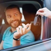 Beautiful bearded man receiving car keys